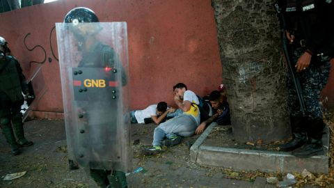 National Police forces detain anti-government protesters near the La Carlota airbase during clashes in Caracas on May 1.