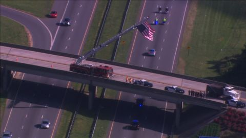 A vehicle carrying Howell's body back to his hometown Thursday, escorted by police, goes under an overpass where a fire crew raised a US flag in tribute.