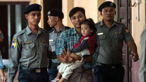 Detained Myanmar journalist Kyaw Soe Oo carrying his daughter is escorted by police for his ongoing trial at a court in Yangon on June 12, 2018.