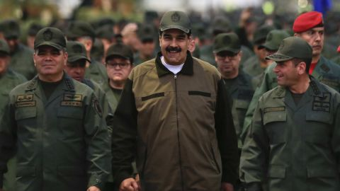 In this handout photo, released by the Miraflores Press Office, Venezuelan President Nicolas Maduro, center, is accompanied by military officers as he arrives for a meeting with troops at Caracas' Fort Tiuna on Thursday, May 2.