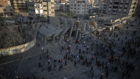 Palestinians inspect the remnants of the Abo Kamar building after airstrikes carried out by Israeli warplanes in Gaza City, Gaza, on Sunday