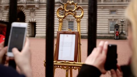 People take pictures of a notice, posted outside Buckingham Palace, that announced the baby's birth.