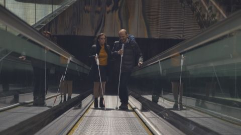 Kursat Ceylan (right) uses the WeWalk smart stick on his way to work