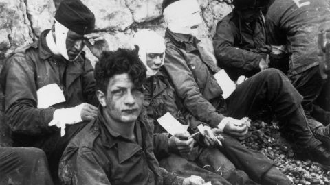 Injured American soldiers wait to be moved to a field hospital after storming Omaha Beach.