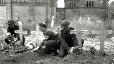 Canadian soldiers place flowers on temporary graves for allied soldiers in Normandy.