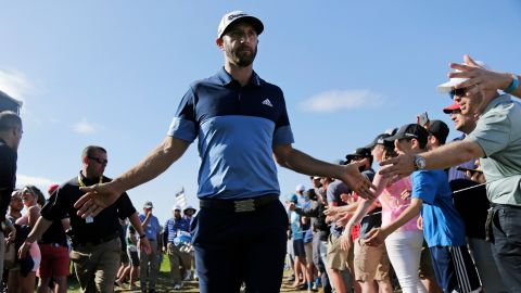 Dustin Johnson greets spectators as he walks to the 12th tee.