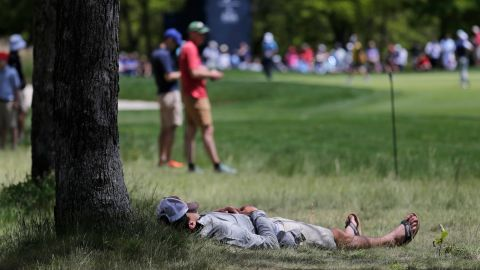 A spectator rests in the shade of a tree along the seventh fairway during the third round.
