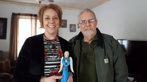 Becca Bundy holds an angel figurine that Bill Cox carved for her before she donated her kidney to him