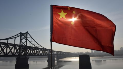 TOPSHOT - The Chinese flag flies on the Yalu River Broken Bridge, with the Sino-Korean Friendship Bridge, and the North Korean city of Sinuiju behind, in the border city of Dandong, in China's northeast Liaoning province on February 23, 2019. - North Korean leader Kim Jong Un's train is expected to cross the Friendship Bridge on a journey across China before Kim's summit meeting with US President Donald Trump in Vietnam on February 27. (Photo by GREG BAKER / AFP)        (Photo credit should read GREG BAKER/AFP/Getty Images)