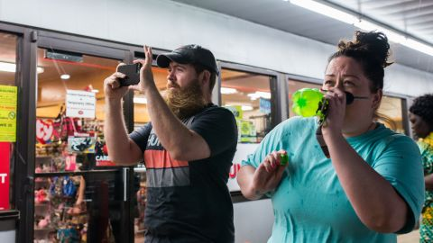Two people stand outside a gas station in Perry, Oklahoma on Monday, May 20 before a windstorm arrives. Many people took shelter in the gas station.