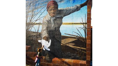 A photo of a 3-year-old girl reaching out to touch the hand of Harriet Tubman has gone viral.