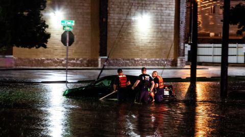 People push a car after it stalled in rising floodwaters in Oklahoma City on May 20.