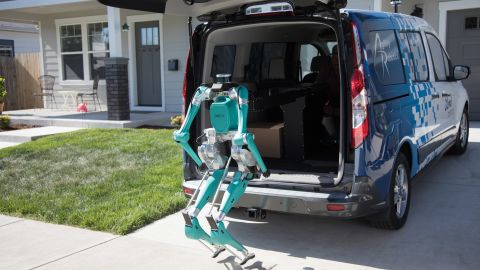 Ford's robot climbs out of a vehicle to make a delivery.