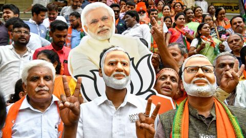 TOPSHOT - Indian supporters and party workers of Bharatiya Janata Party (BJP) wear masks of Indian Prime Minister Narendra Modi and flash victory signs as they celebrate on the vote results day for India's general election in Bangalore on May 23, 2019. - Indian Prime Minister Narendra Modi looked on course on May 23 for a major victory in the world's biggest election, with early trends suggesting his Hindu nationalist party will win a bigger majority even than 2014. (Photo by MANJUNATH KIRAN / AFP)        (Photo credit should read MANJUNATH KIRAN/AFP/Getty Images)