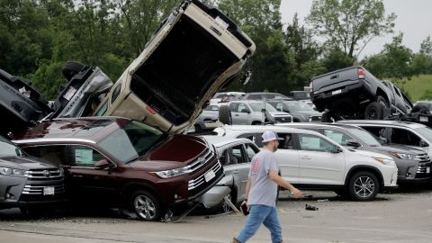 A worker walks past tornado-damaged Toyotas at a dealership in Jefferson City, Mo., Thursday, May 23, 2019 after a tornado tore though late Wednesday. (AP Photo/Charlie Riedel)