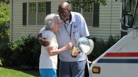 Lorraine Wascher, a stop on Martin's route for more than 20 years, shares a hug with the retiring worker.