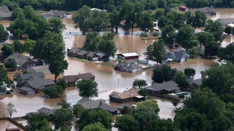 In this aerial image, homes are inundated with flood waters from the Arkansas River near South 145th West Ave near Highway 51 on Thursday, May 23, 2019, in Sand Springs, Okla. Storms and torrential rains have ravaged the Midwest, from Texas through Oklahoma, Kansas, Nebraska, Iowa, Missouri and Illinois, in the past few days. (Tom Gilbert/Tulsa World via AP)