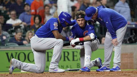 A distraught Chicago Cubs' Albert Almora Jr., center, kneels as Jason Heyward, left, and manager Joe Maddon, right, talk to him after a foul ball Almora hit into the stands during the fourth inning of a baseball game against the Houston Astros hit a child.