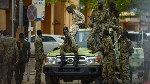 Sudanese army soldiers gather as people rally in front of the Presidential Palace in downtown Khartoum on May 18.