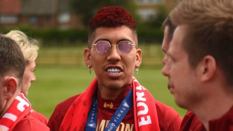Liverpool's Brazilian midfielder Roberto Firmino shows off his celebratory red hairstyle <br />during an open-top bus parade around the city on Sunday.