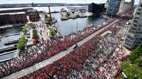 Football fans line the streets waiting to see the Liverpool football team take part in an open-top bus parade around Liverpool on Sunday.