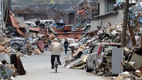 A resident cycles on the street amongst tsunami generated debris in Kamaishi, Iwate prefecture on May 6, 2011. The March 11 earthquake and subsequent tsunami left some 26,000 dead or missing and obliterated whole towns and villages on the northeast coast.    AFP PHOTO / TOSHIFUMI KITAMURA (Photo credit should read TOSHIFUMI KITAMURA/AFP/Getty Images)