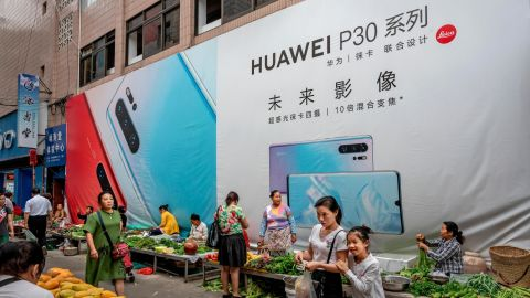 MANGSHI, CHINA - JUNE 1: A woman shops with her daughter in front of a billboard advertising smartphones for China's Huawei Technologies Co., at a market on June 1, 2019 in Mangshi, Yunnan Province, southwestern China. (Photo by Kevin Frayer/Getty Images)