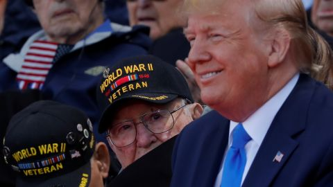 A World War II veteran looks over Trump's shoulder during the commemoration ceremony.