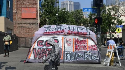 Pedestrians walk past a tent for the homeless on a sidewalk in Skid Row, downtown Los Angeles, on May 30, 2019. - The city of Los Angeles on May 29 agreed to allow homeless people on Skid Row to keep their property and not have it seized, providing the items are not bulky or hazardous. (Photo by Frederic J. BROWN / AFP)        (Photo credit should read FREDERIC J. BROWN/AFP/Getty Images)