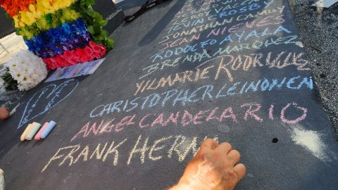 Edwin Rodriguez writes the names of the victims of the Pulse shooting in the front of the nightclub in June 2016 in Orlando, Florida.