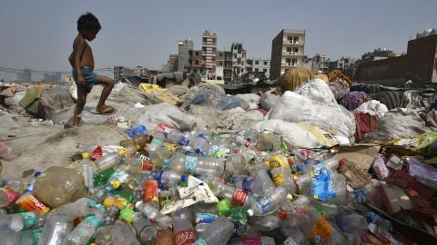 NEW DELHI, INDIA - JUNE 4:  A boy looks for recyclable material as piles of plastic lie on the bank of Yamuna on a hot summer day, near Okhla on June 4, 2019 in New Delhi, India.  World Environment Day is marked anually on June 5. (Photo by Biplov Bhuyan/Hindustan Times via Getty Images)