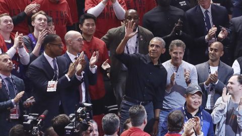 Former US President Barack Obama waves to the crowd while attending Game 2 in Toronto.