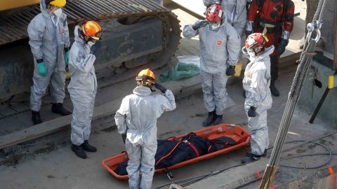 Rescue workers recover a body as the boat is raised.