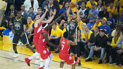 Three Raptors defend Stephen Curry in the first half of Game 6.