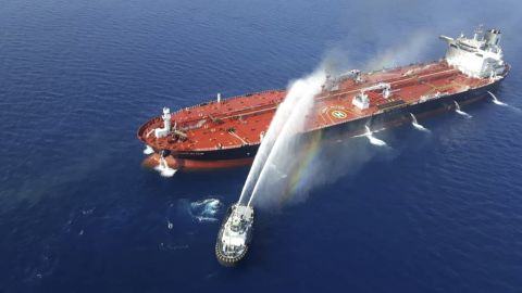 An Iranian navy boat sprays water to extinguish a fire on an oil tanker in the sea of Oman, Thursday, June 13, 2019.