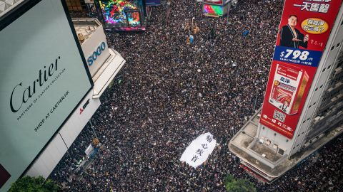 Protesters hold banners and shout slogans as they march on a street on June 16 in Hong Kong.