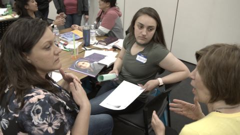 Three members of a mental health first aid class in Defiance, Ohio discuss the results of a psychosis exercise.