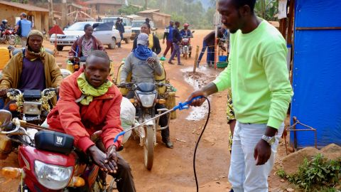 A motorcycle taxi driver gets his hands washed with a chlorine solution at a checkpoint between Beni and Butembo in Eastern DRC. Temperatures are also checked and possible Ebola isolated. Still, many Ebola victims have travelled far distances and infected new parts of North Kivu and Ituri provinces.