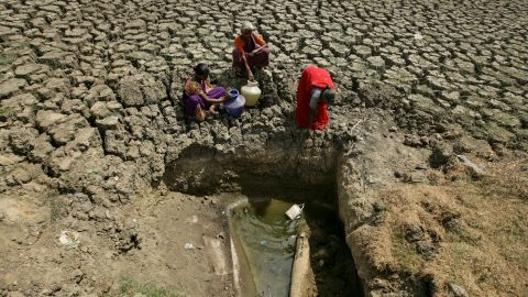 Women fetch water from an opening made by residents at a dried-up lake in Chennai, India.