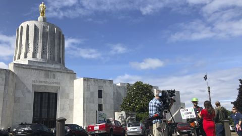 A TV reporter interviews self-employed logger Bridger Hasbrouck, of Dallas, Ore., outside the Oregon State House in Salem, Ore., on Thursday, June 20, 2019, the day the Senate is scheduled to take up a bill that would create the nation's second cap-and-trade program to curb carbon emissions. Senate Republicans, however, pledged to walk out so there wouldn't be enough lawmakers present for a vote on House Bill 2020, which is extremely unpopular among loggers, truckers and many rural voters. (AP Photo/Gillian Flaccus)
