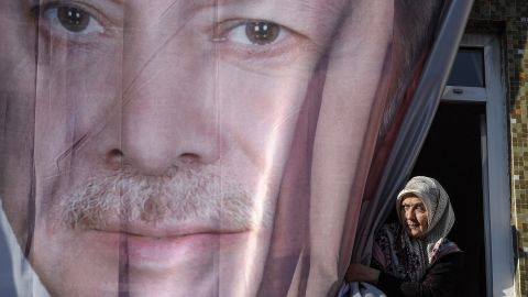 A woman peers out from behind a giant poster of Erdogan during a rally in Kasimpasa on March 5.