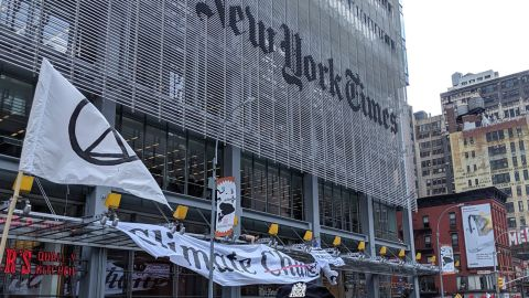 Signs and flags are seen waving outside of The New York Times offices in New York during the protest Saturday.