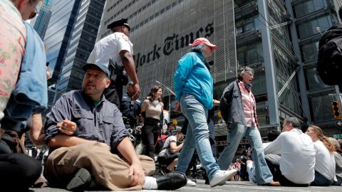 Activists sit on an intersection as others are taken into custody by New York Police officers during a climate change rally outside of the New York Times building.