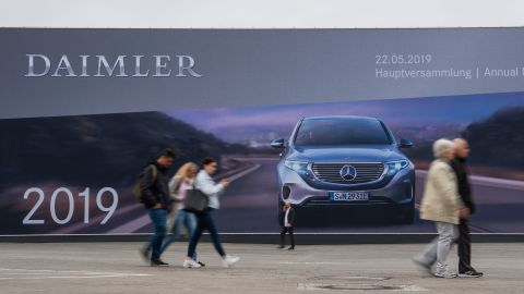 People walk past a giant billboard advertising German car manufacturing giant Daimler's annual general meeting on May 22, 2019 in Berlin. - Daimler boss Dieter Zetsche, 66, bows out after 13 years on with his Swedish successor Ola Kallenius needing to tackle problems brewing under the bonnet of the Mercedes-Benz maker. (Photo by John MACDOUGALL / AFP)        (Photo credit should read JOHN MACDOUGALL/AFP/Getty Images)