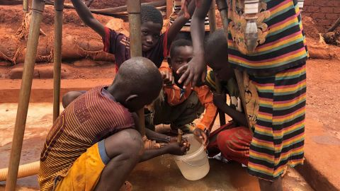 Children gather water at a filling station in the camp at Bria.