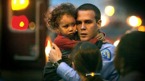 In this November 17, 2003 photo, St. Louis Police officer Michael Langsdorf comforts 2-year-old KeAndre Colenburg who had just been dropped by his father from the third floor roof of a house after the house caught on fire (J.B. Forbes/St. Louis Post-Dispatch via AP)