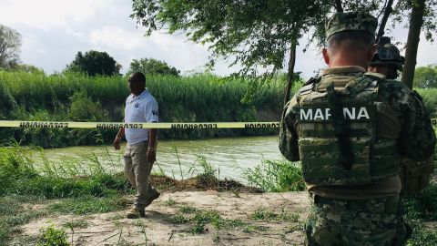 Mexican authorities walk along the Rio Grande bank where the bodies of the father and child were found.