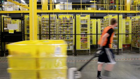 An employee pulls a pallet jack carrying plastic crates past goods in storage units at the Amazon.com Inc. fulfillment center in Robbinsville, New Jersey, U.S., on Thursday, June 7, 2018. Seattle-based Amazon hasn't yet announced the exact date for this year's Amazon Prime Day, the e-commerce giants big July sales promotion. Photographer: Bess Adler/Bloomberg via Getty Images