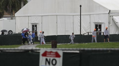 Migrant children and employees walk on the grounds of the Homestead shelter in Florida.