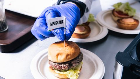 A technician places a flag toothpick into a burger with an Impossible burger patty at the test kitchen inside Impossible Foods headquarters in Redwood City, Calif. on Thursday, June 20, 2019.